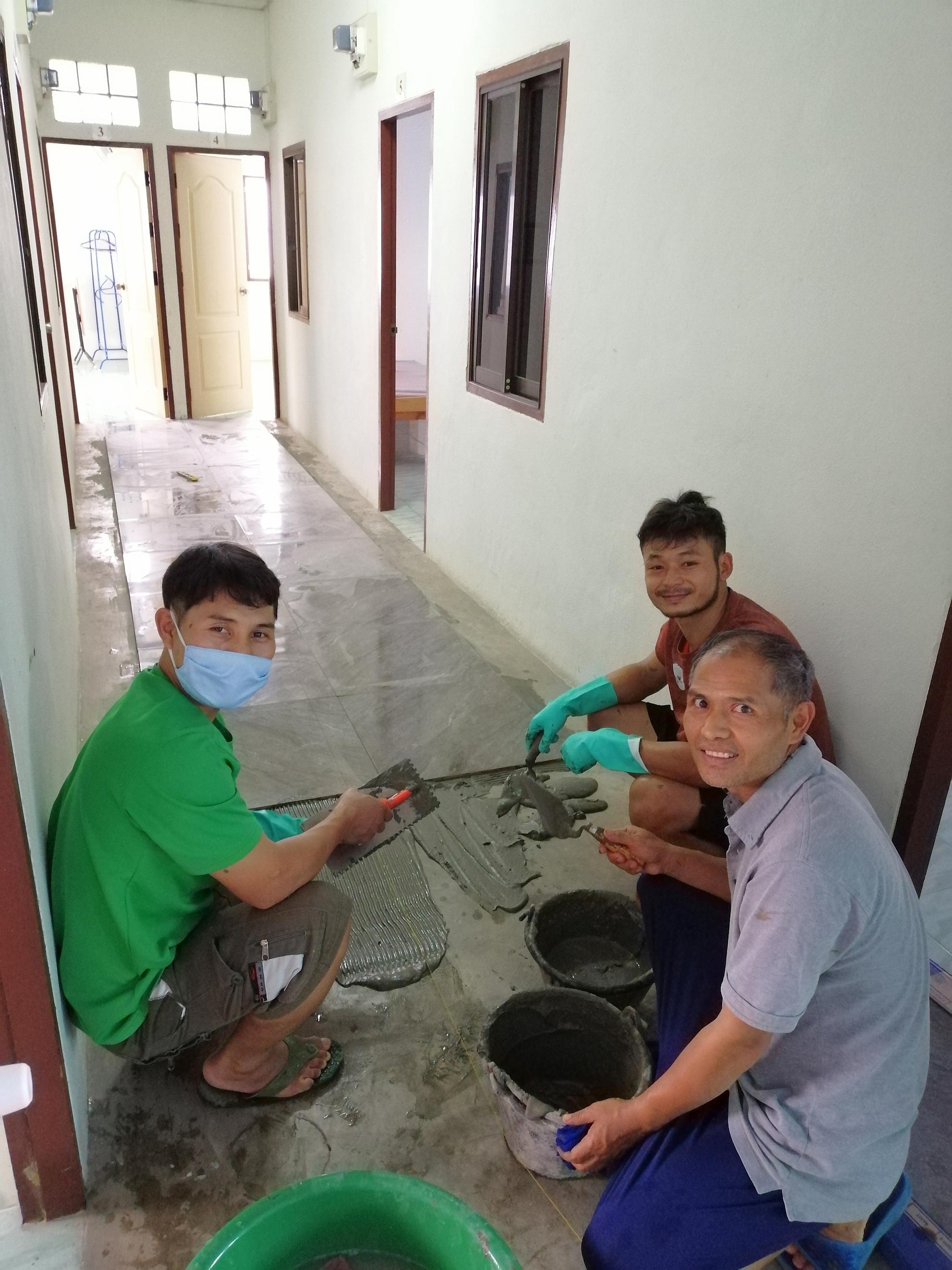 三位忠心的男同工 炎熱的天氣下在工樓客房舖地磚