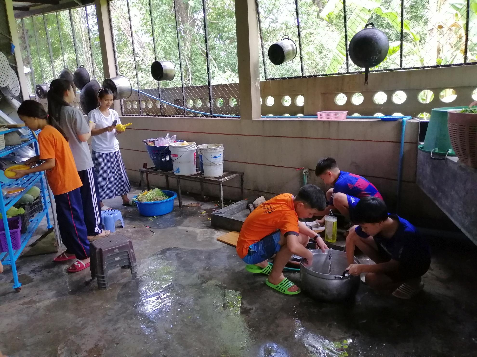 新天學生中心的孩子回來了 飯後男生洗鍋 女生切芒果