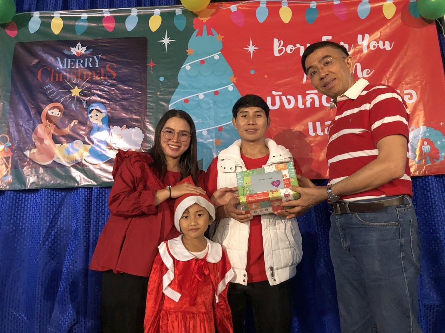 在聖誕晚會上,傅牧師致送禮物給快將生產的同工蘇慈恩(左一)蘇德禮家庭